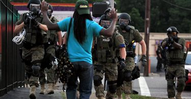 a picture of police wearing riot gear to arrest an unarmed black man raises questions about police use of excessive force.